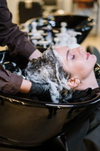 woman getting hair washed with caffeine shampoo
